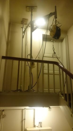 Piperør heises opp til loft gjennom trappeløp.